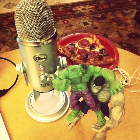 Still life photograph of a microphone, two Hulks fighting, and a slice of pizza.