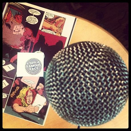 Still life photograph of a microphone and an open comic book.