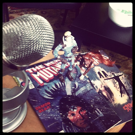 Still life photograph of a microphone and an action figure.