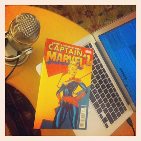 Still life photograph of a microphone, Captain Marvel comic, and a MacBook.