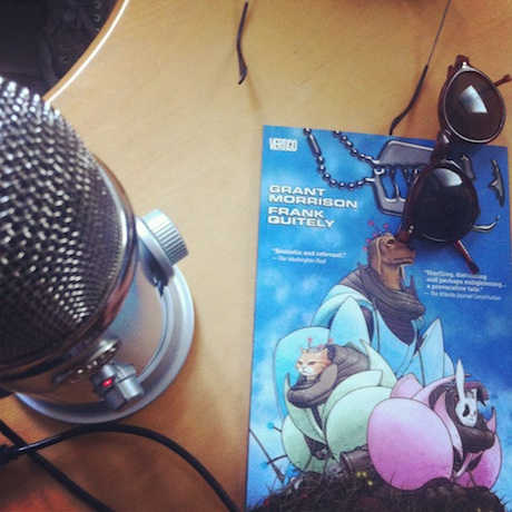 Photograph of microphone, comic book, and a pair of sunglasses.