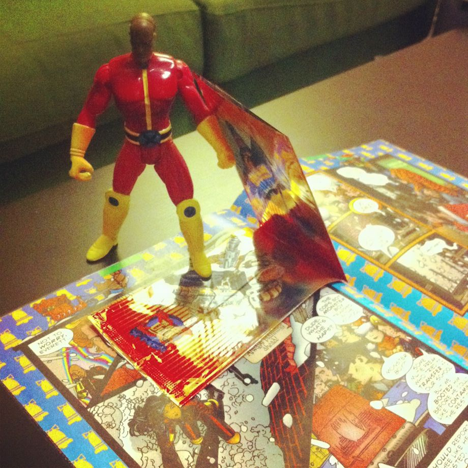action figure standing on open comic book