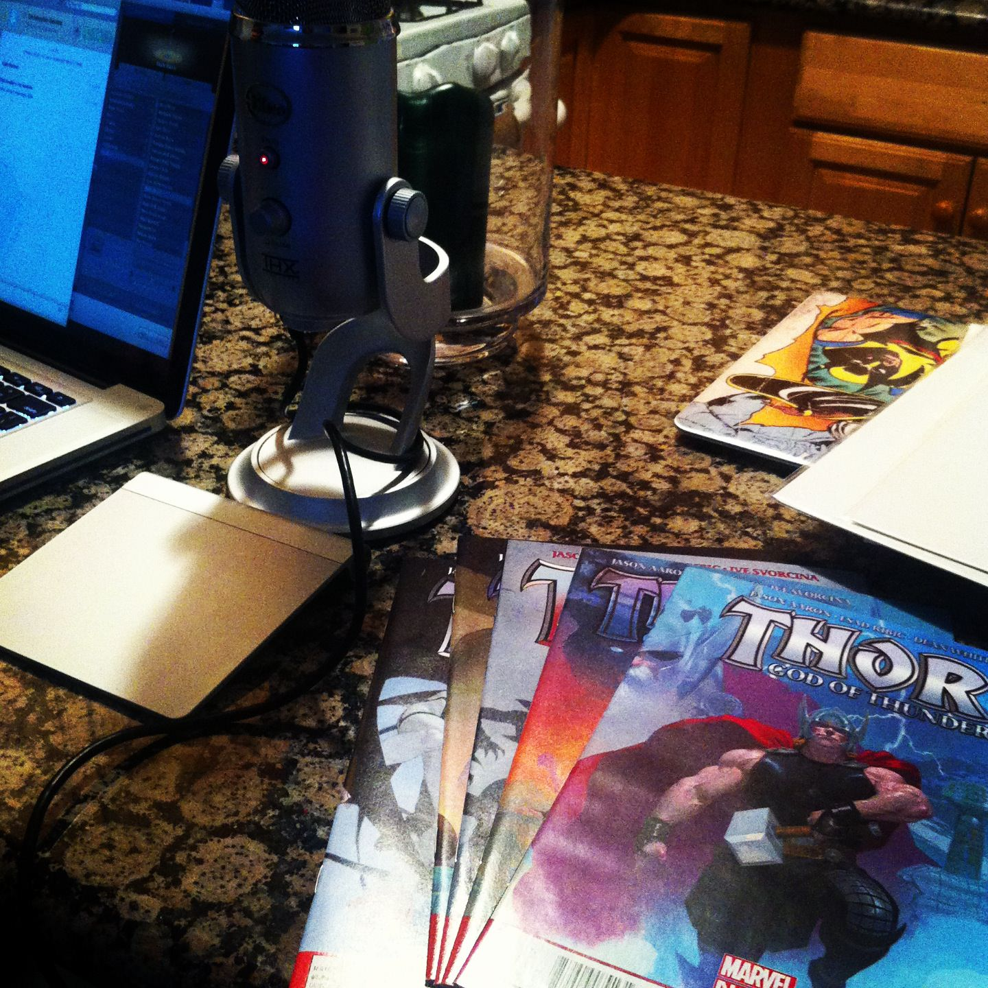 Photo of a microphone and some Thor comic books on a table.